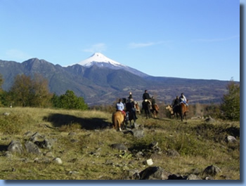 Group of riders on horseback in front of Villarrica Volcano on a horseback trail ride in chilean andes