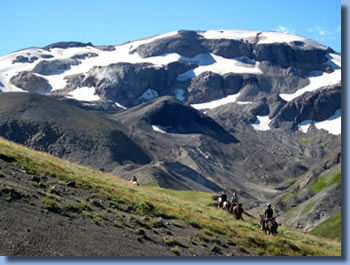 Group of riders in fron of a snowcaped mountain on a trail ride in southern Chile