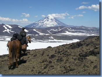 Group of riders on horseback in front of Lanin Volcanoe on a horseback trailride in chilean andes