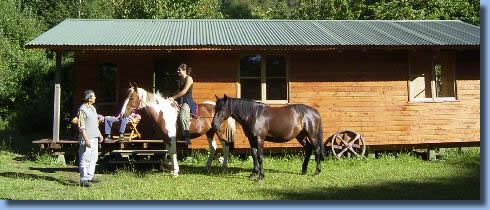 2 horses and riders in front of Cabin at Antilco the horse riding ranch in Chile